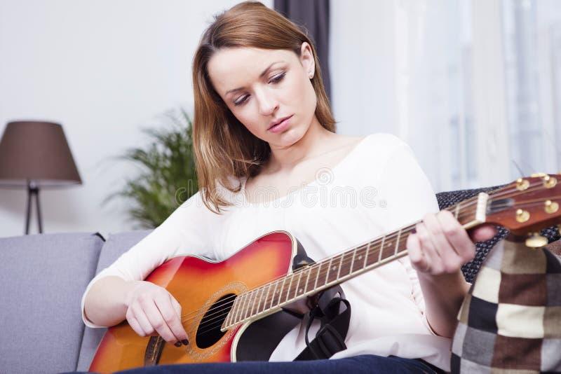 Jong meisje op bank het spelen gitaar stock afbeelding