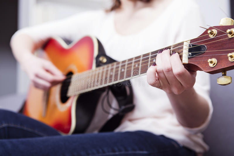 Jong meisje op bank het spelen gitaar stock foto