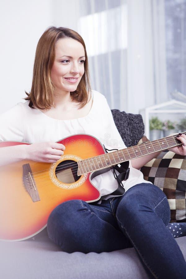 Jong meisje op bank het spelen gitaar royalty-vrije stock foto