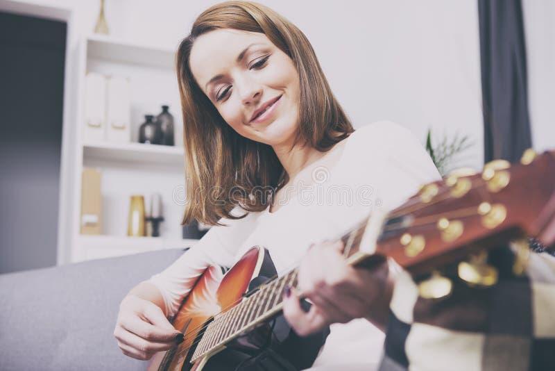 Jong meisje op bank het spelen gitaar stock afbeeldingen
