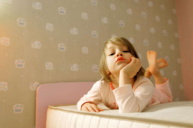 Jong meisje op bed stock afbeeldingen