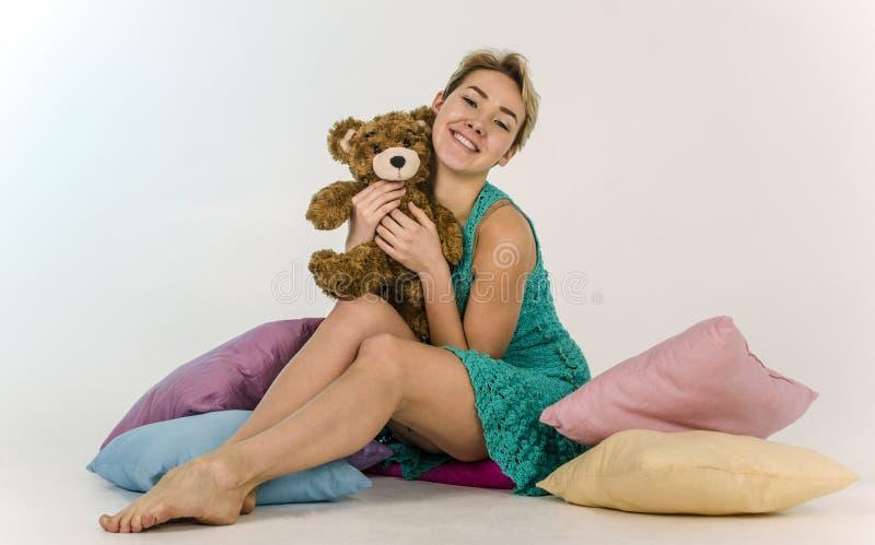 Jong meisje op een bed met een teddybeer stock foto's