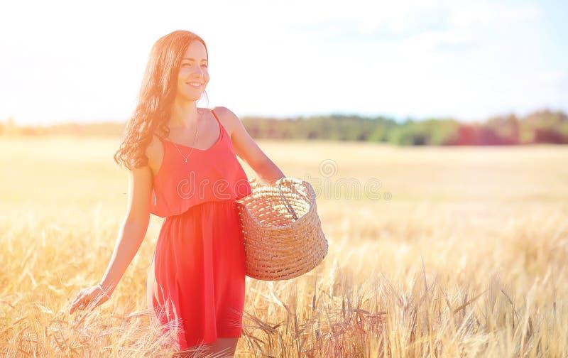 Jong meisje op een tarwegebied De zomerlandschap en een meisje op een Na stock fotografie