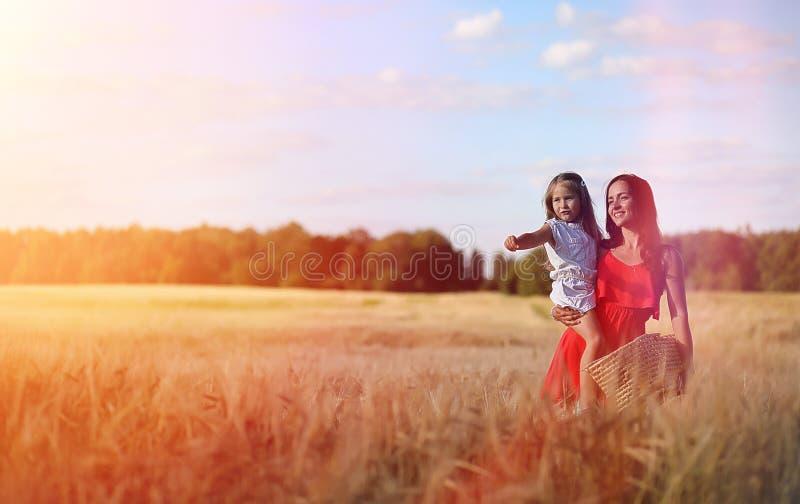 Jong meisje op een tarwegebied De zomerlandschap en een meisje op een Na stock afbeelding