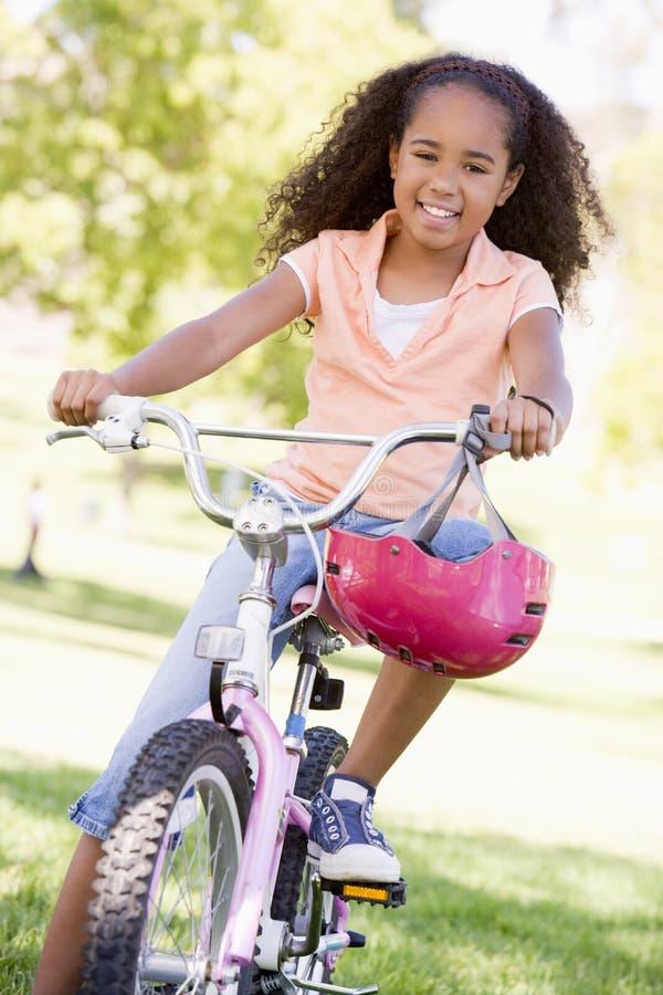 Jong meisje op fiets die in openlucht glimlacht royalty-vrije stock foto