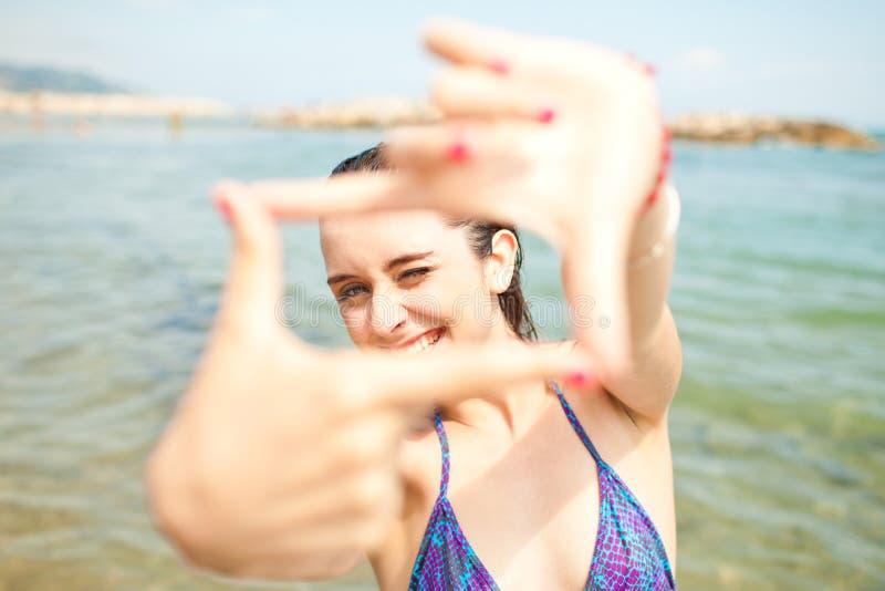 Jong meisje op het strand dat fotoframe maakt stock afbeeldingen