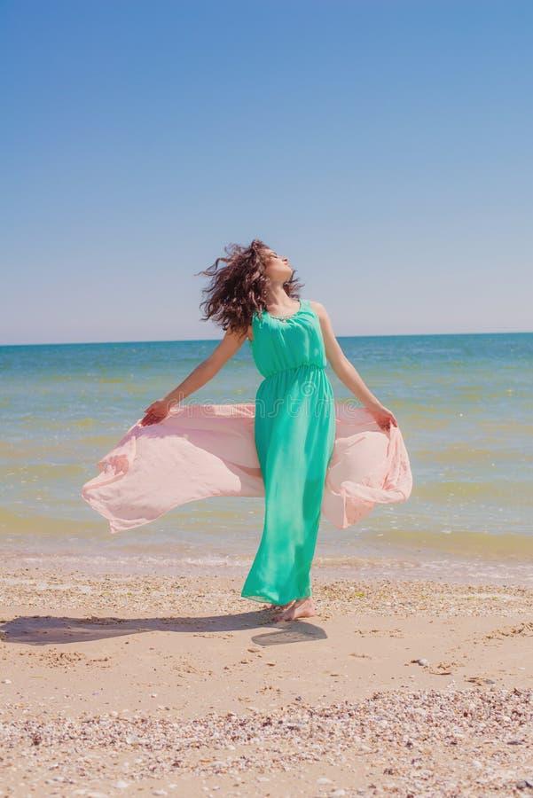 Jong meisje op het strand in de zomer met een vliegende sjaal stock fotografie