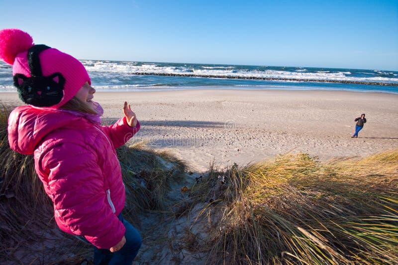 Jong meisje op strand die aan haar moeder golven stock afbeelding