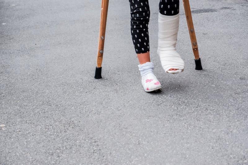 Jong meisje in orthopedisch gegoten op steunpilaren die op de straat dichtbij de weg lopen Kind met een gebroken been op steunpil stock afbeelding