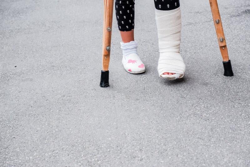 Jong meisje in orthopedisch gegoten op steunpilaren die op de straat dichtbij de weg lopen Kind met een gebroken been op steunpil stock fotografie