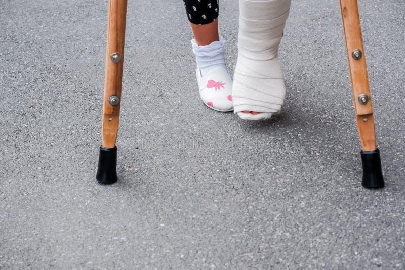 Jong meisje in orthopedisch gegoten op steunpilaren die op de straat dichtbij de weg lopen Kind met een gebroken been op steunpil royalty-vrije stock foto's