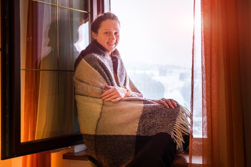 Jong meisje in plaid op een venstervensterbank in de winter stock foto's