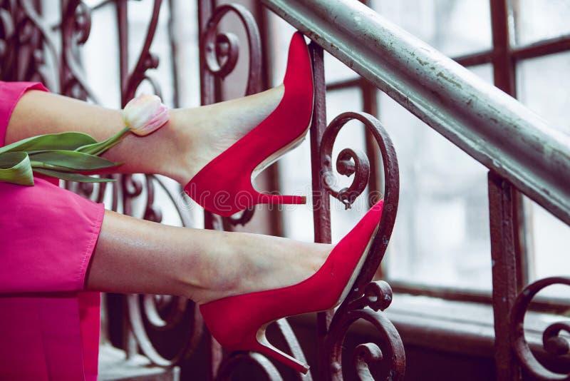 jong meisje in rode schoenen met een tulp stock fotografie