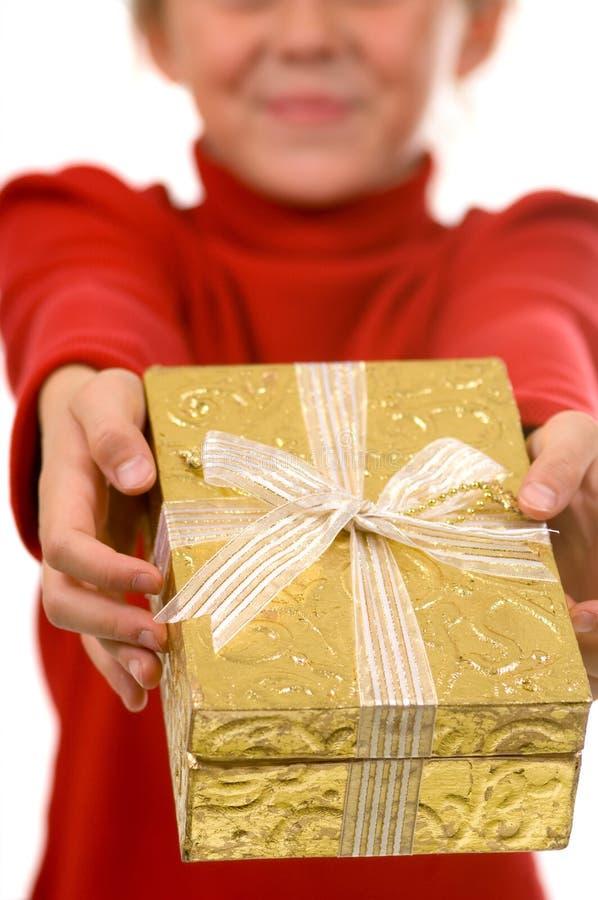 Jong meisje in rood met gouden aanwezige Kerstmis stock foto