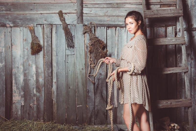 Jong meisje in schuur met een kabel in haar handen stock afbeeldingen