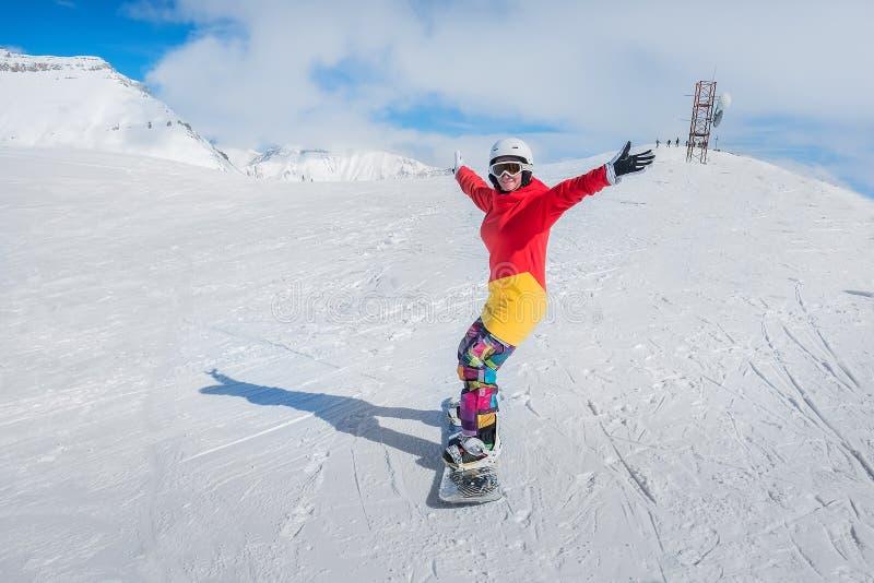 Jong meisje snowboarder in motie op snowboard in bergen royalty-vrije stock fotografie