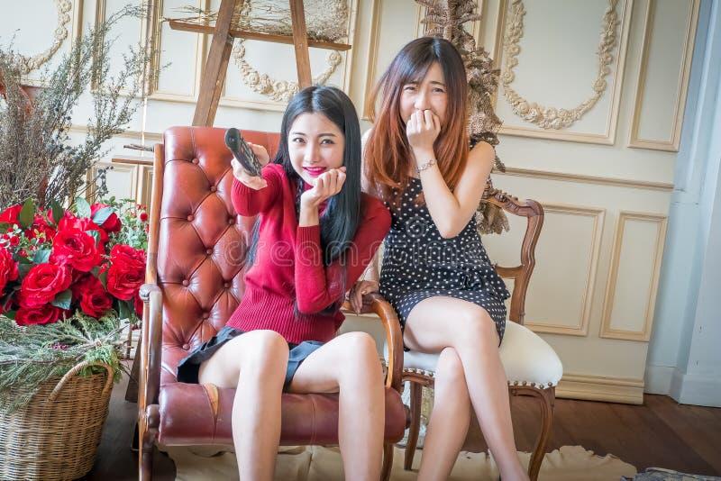 Jong meisje twee die een afstandsbediening het letten op film houden royalty-vrije stock foto's
