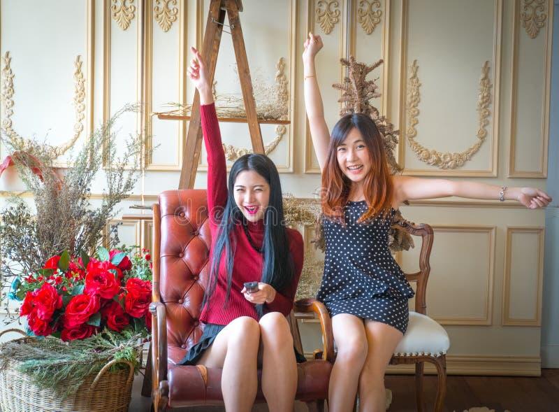 Jong meisje twee die een afstandsbediening het letten op toejuichingsport houden stock foto