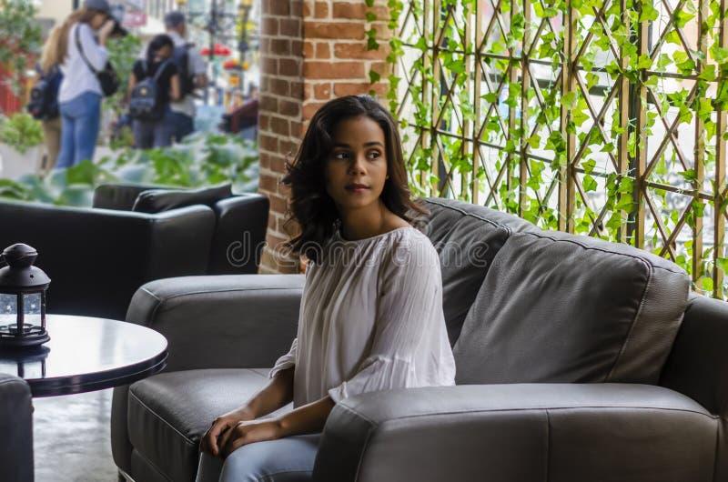 jong meisje van 19 tot 25 jaar oude zittings op zwarte bank in restaurant die uit het venster kijken royalty-vrije stock foto's