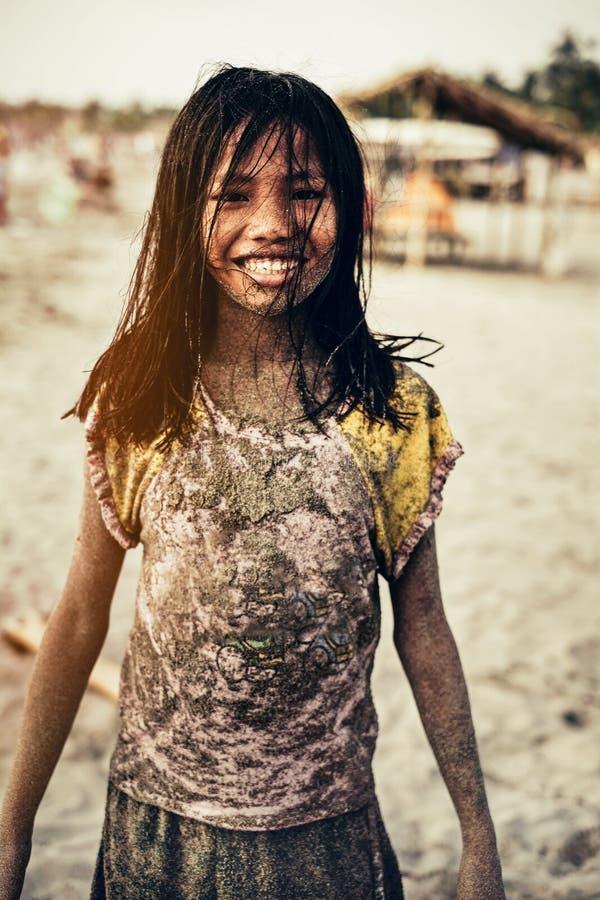 Jong meisje vuil van zand op het strand stock foto's