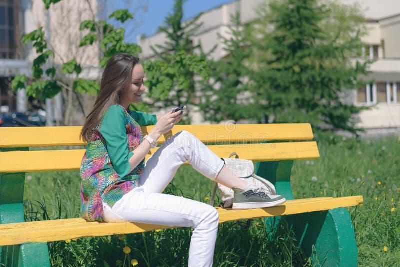 Jong meisje in witte jeans en tennisschoenen op een gele bank en gebruik die een smartphone, online mededeling, sociale netwerken royalty-vrije stock afbeeldingen
