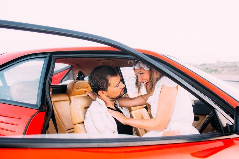 Jong meisje in witte kleding en mensenzitting op de voorzetel van de rode auto stock afbeelding