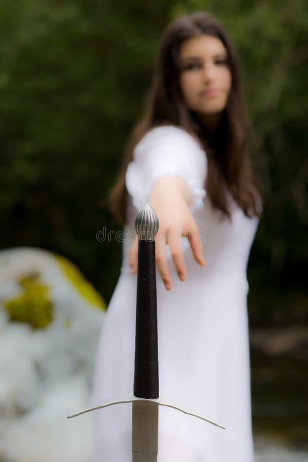 Jong meisje in witte kleding met zwaard met twee handen stock afbeelding