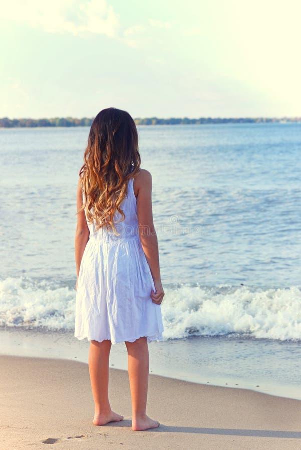 Jong meisje in witte kleding op strand royalty-vrije stock afbeelding