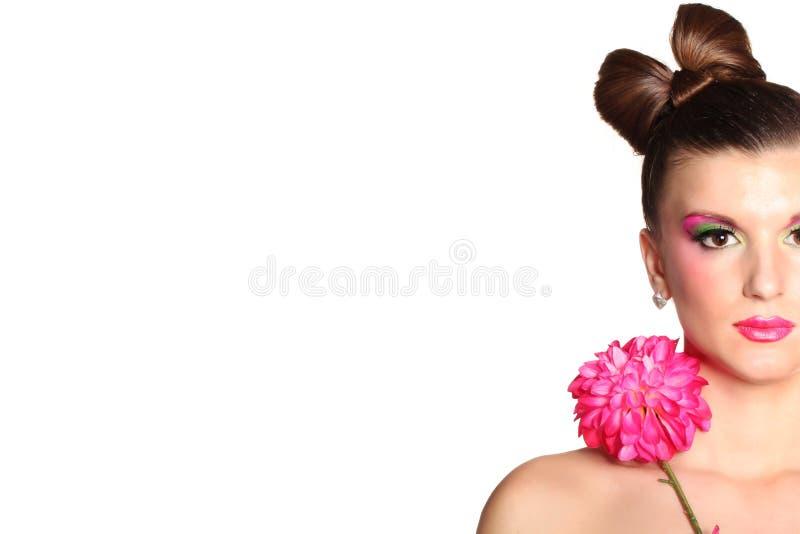 Jong meisje zoals een pop in roze kleding met bloem royalty-vrije stock fotografie