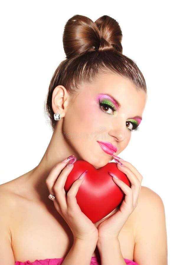 Jong meisje zoals een pop in roze kleding met hart royalty-vrije stock afbeelding
