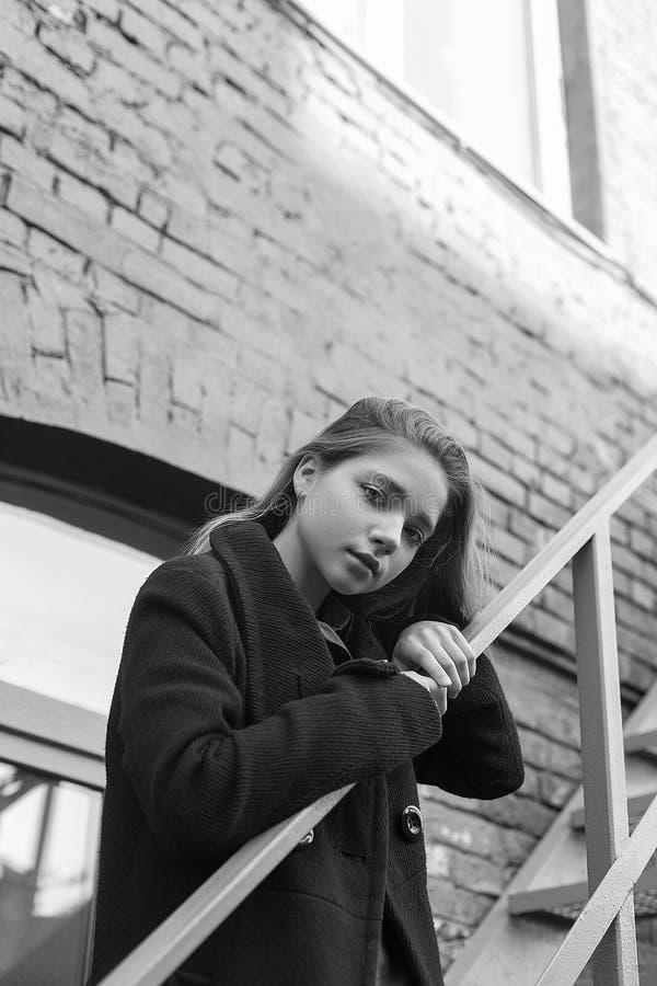 Jong meisje in zwarte laag die zich op treden met bakstenen muur op achtergrond bevinden Concept eenzaamheid Zwart-wit beeld royalty-vrije stock fotografie