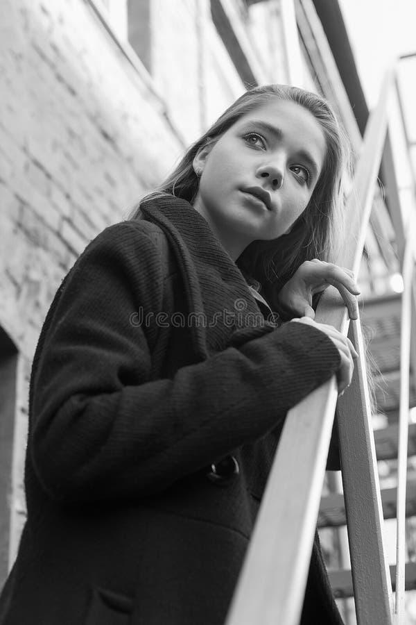 Jong meisje in zwarte laag die zich op treden met bakstenen muur op achtergrond bevinden Concept eenzaamheid Zwart-wit beeld stock afbeelding