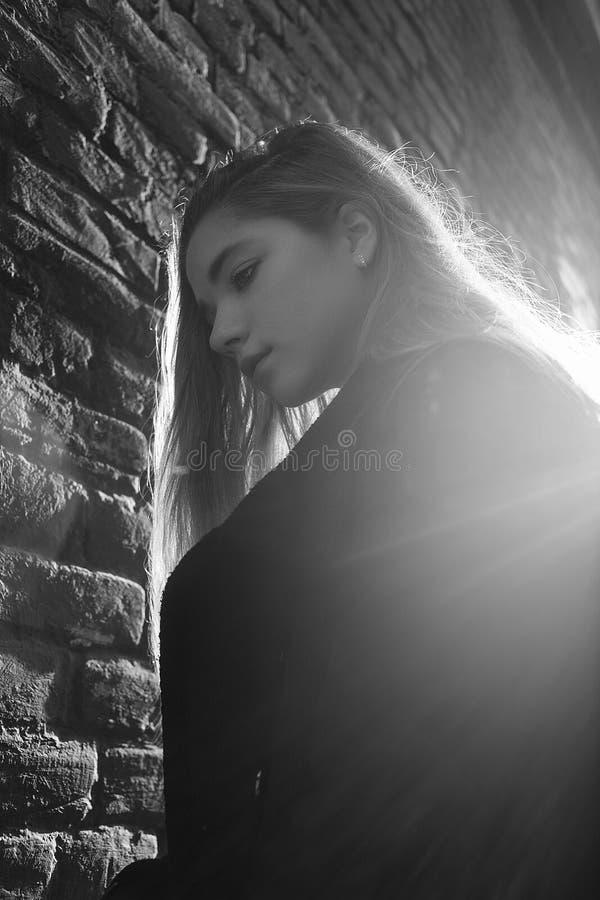 Jong meisje in zwarte laag die zich voor een bakstenen muur in mooie zonsondergang bevinden backlight Concept eenzaamheid stock afbeelding