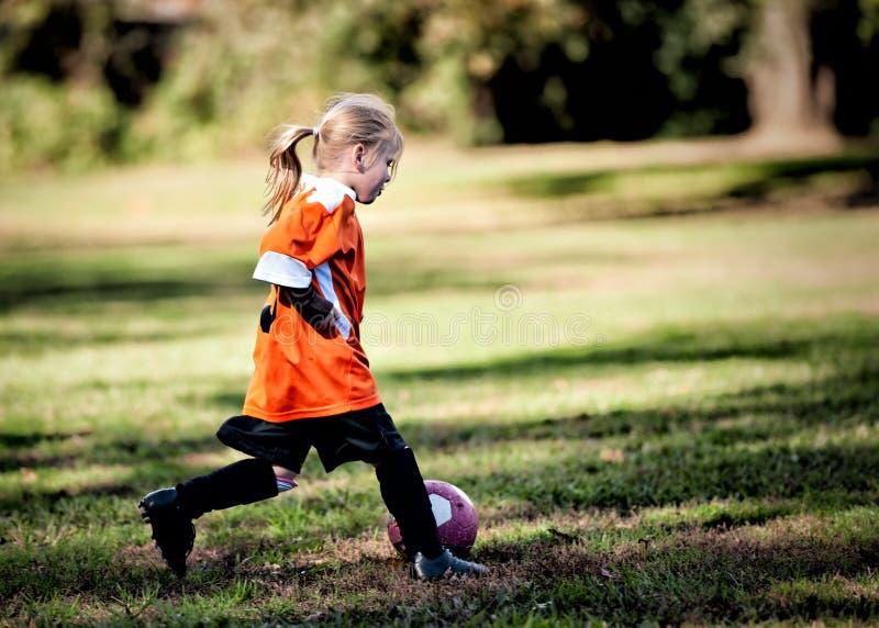 Jong meisjes speelvoetbal stock fotografie