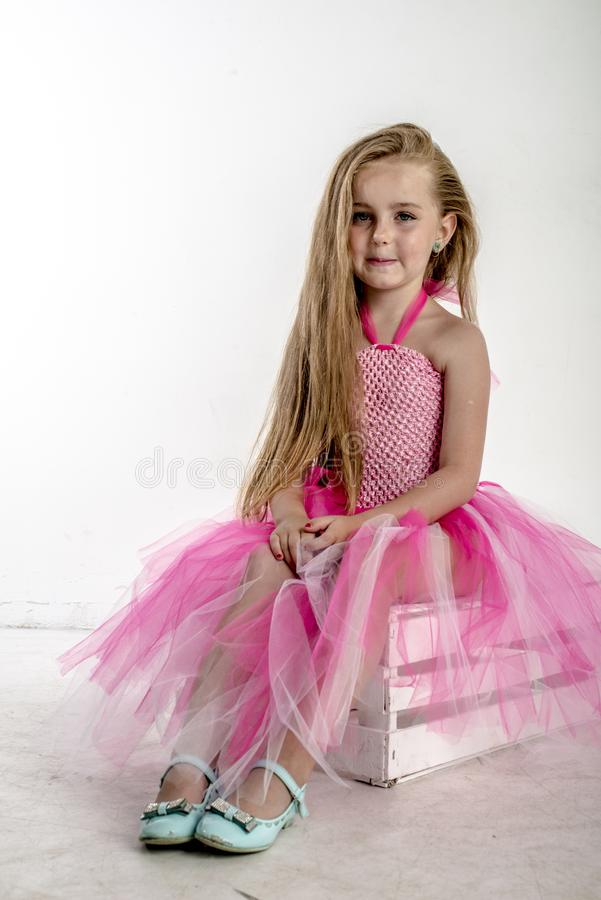 Jong meisjeskind in een roze feestelijke kleding met wit blondehaar royalty-vrije stock afbeelding