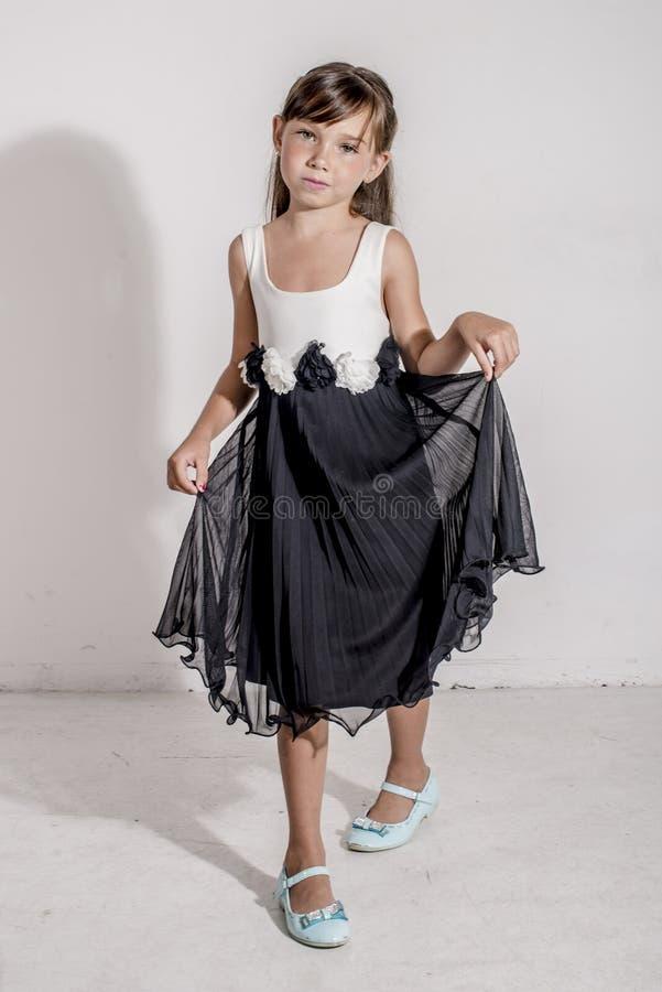 Jong meisjeskind in een zwart-witte feestelijke kleding met brunetttehaar stock afbeelding