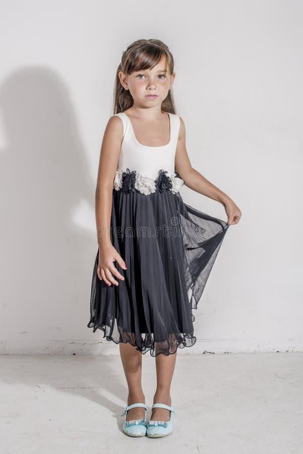 Jong meisjeskind in een zwart-witte feestelijke kleding met brunetttehaar royalty-vrije stock foto
