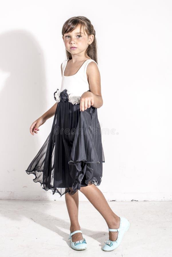 Jong meisjeskind in een zwart-witte feestelijke kleding met brunetttehaar royalty-vrije stock afbeelding