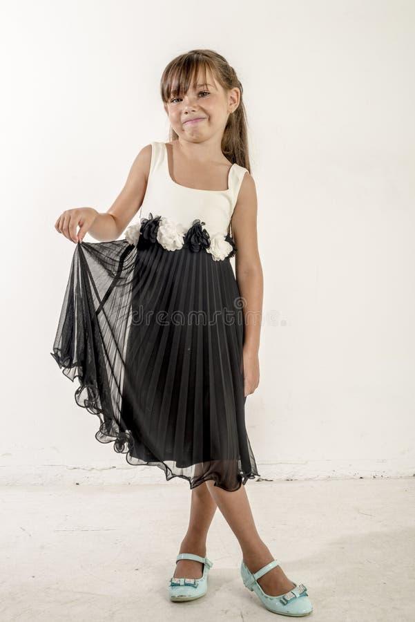 Jong meisjeskind in een zwart-witte feestelijke kleding met brunetttehaar stock afbeeldingen
