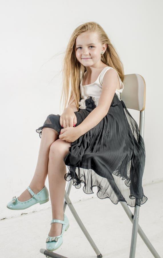 Jong meisjeskind in een zwart-witte feestelijke kleding met wit blondehaar royalty-vrije stock foto