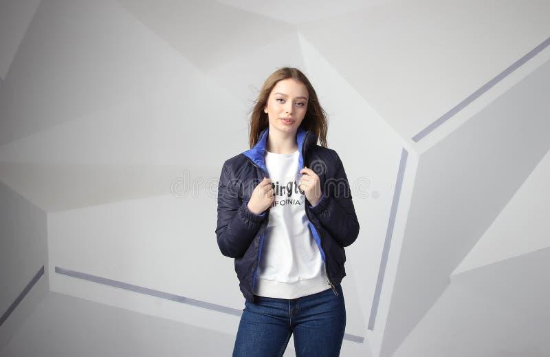 Jong meisjesmeisje die jasje met gebied voor uw embleem dragen, prototype van witte vrouwen hoodie royalty-vrije stock foto