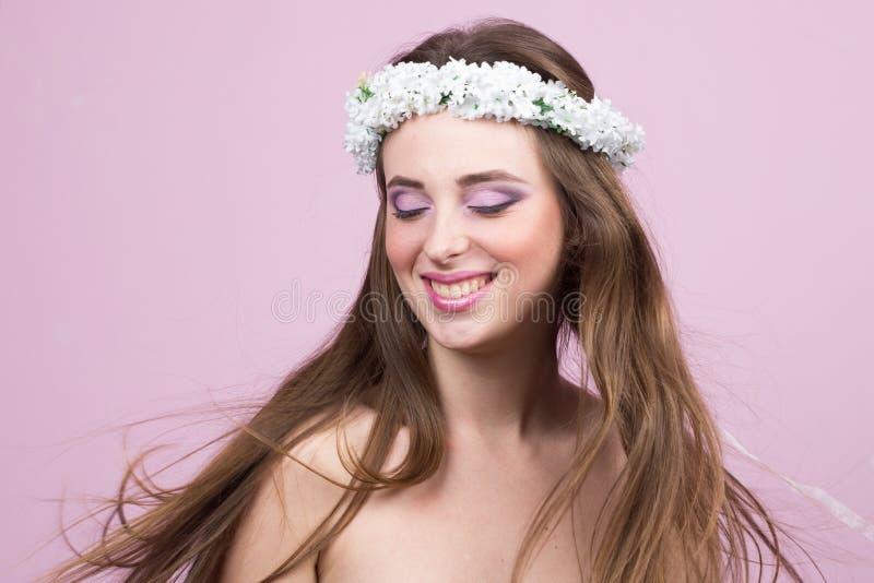 Jong model met heldere bloemen op haar hoofd stock foto's