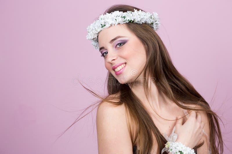Jong model met heldere bloemen op haar hoofd royalty-vrije stock afbeelding