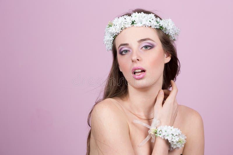 Jong model met heldere bloemen op haar hoofd stock fotografie