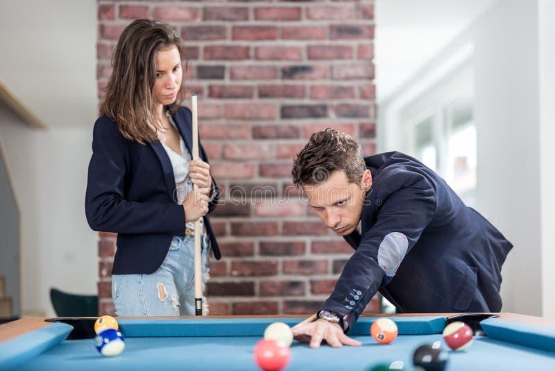 Jong modern paar in spel van het de lijstbiljart van de liefde het speelpool stock fotografie