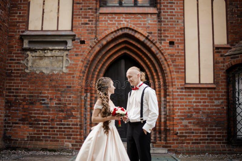 Jong modieus echtpaar die en zich op de achtergrond van oude de bouwboog bevinden glimlachen royalty-vrije stock afbeeldingen