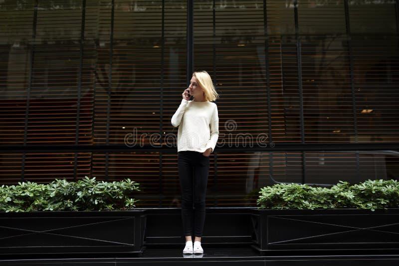 Jong modieus en slank meisje die zich dichtbij het restaurant bevinden en op de telefoon spreken stock fotografie