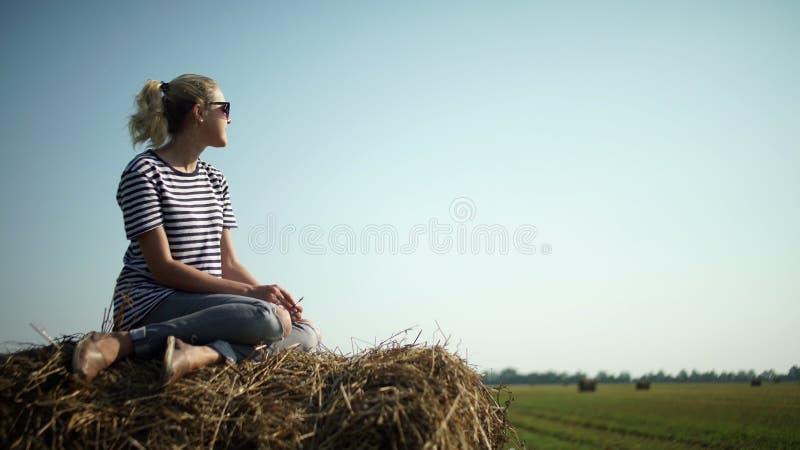 Jong modieus meisje in een gestreepte t-shirtzitting op een hooiberg royalty-vrije stock foto