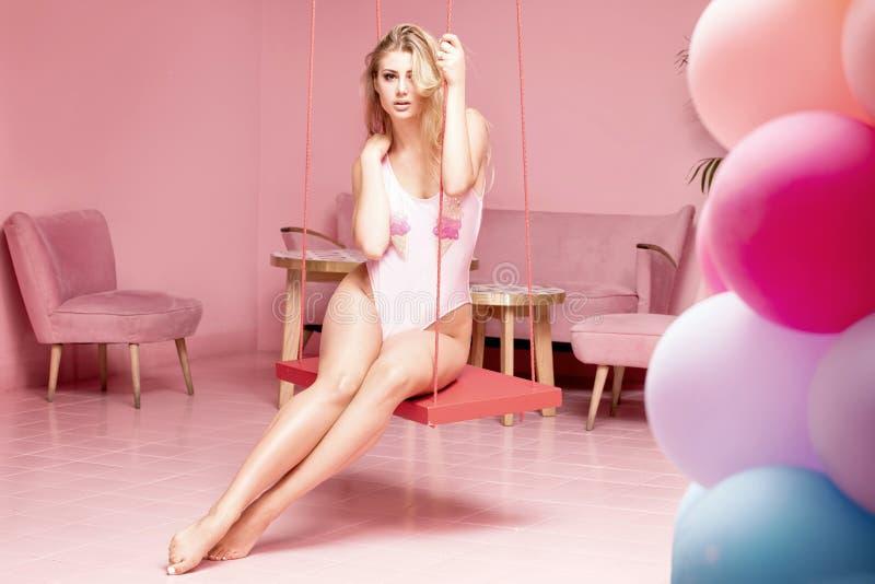 Jong modieus meisje in roze binnenland stock fotografie