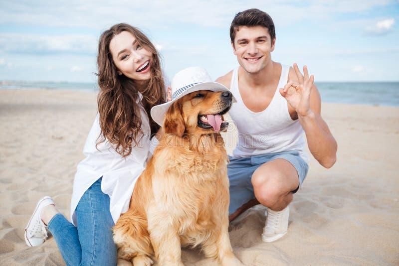 Jong modieus mooi paar in liefdezitting het spelen met hond stock afbeeldingen